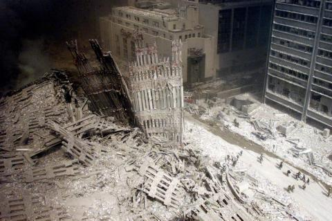 A group of firefighters walk amid rubble near the base of the destroyed south tower of the World Trade Center in New York on September 11, 2001. In the worst terror attack on the U.S. mainland in modern history, two hijacked planes slammed into the twin towers of the World Trade Center in New York and a third plane hit the Pentagon, across the Potomac river from Washington. REUTERS/Peter Morgan PP03080044 AS